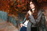 Outdoor fashion portrait of young beautiful fashionable woman wearing white turtleneck, grey checked blazer, wrist watch, holding small leather bag, posing in autumn street. Copy, empty space for text - 229353493