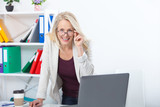 Her job is her life. Business woman with glasses working in office with documents. Beautiful middle aged woman looking at camera with smile while siting in the office. - 229355410