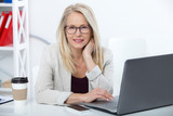 Her job is her life. Business woman with glasses working in office with documents. Beautiful middle aged woman looking at camera with smile while siting in the office. - 229355449