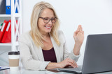 Happy businesswoman with glasses working, chating with laptop at office - 229355456