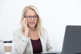 Listening to clients requirements. Beautiful middle aged woman with glasses talking on smart phone and smiling at her working place siting in the office. - 229355476