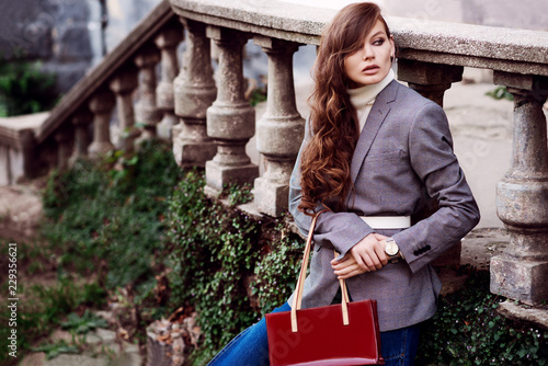 Leinwandbild Motiv Outdoor fashion portrait of young beautiful fashionable woman wearing white turtleneck, grey checked blazer, wrist watch, holding red bag, posing in street. Copy, empty space for text