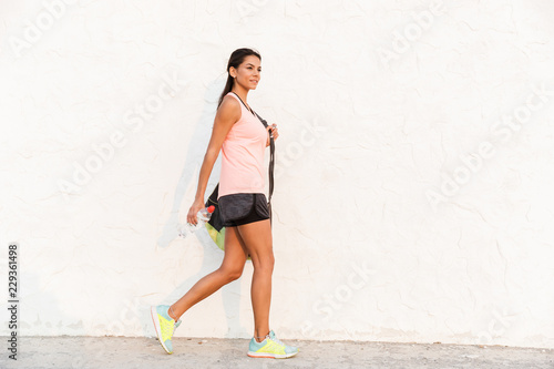 Cheerful young sportswoman holding water bottle - 229361498