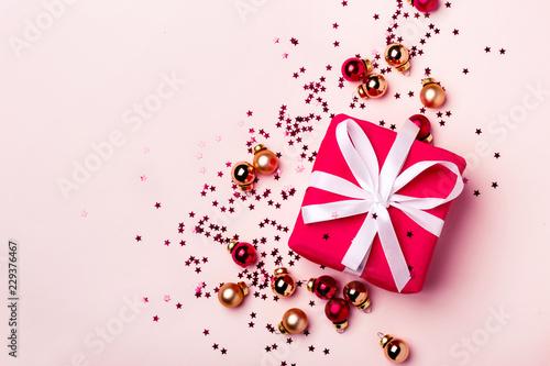 Bożenarodzeniowy pastelowy tło z prezentem i piłki confetti