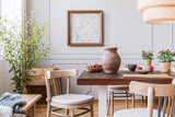 Clay vase on the table in a dining room interior with a plant, chairs and art on a wall - 229383886