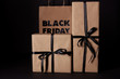wrapped gift boxes and black friday shopping bag on black surface