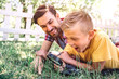Leinwanddruck Bild - Adult and child are lying on grass outside in park. Boy is looking down through loop. He is amazed. His dad is besides him. He is looking at his son and smiling. Adult is happy.