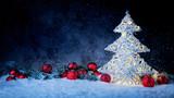 Leuchtender Weihnachtsbaum mit Weihnachtskugeln und Tannenzweig vor dunklem Hinterdrund mit Schnee - 229391809
