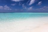Tropischer Traumstrand mit türkisem Wasser und feinem Sand unter tiefblauem Himmel