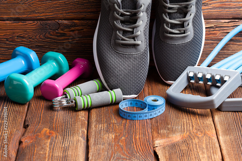 Various sports accessories - dumbbells, sport shoes and measuring tape on wooden background