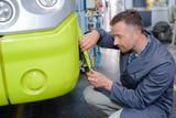 Man fitting fairing to bus - 229403224