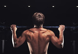 Rear view of muscular man doing pull up exercise on horizontal bar. Male athlete working out in the gym - 229404807