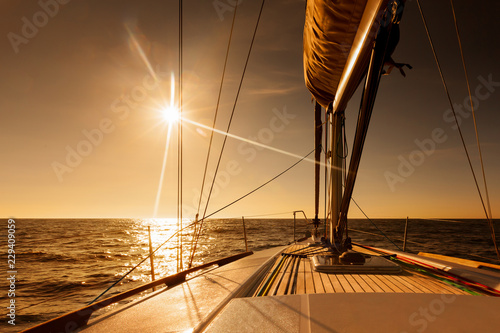 Sailing towards sunset at open sea
