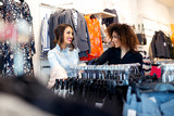 Two young girls look at clothing in store - 229413239