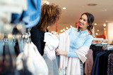 Two young girls look at clothing in store - 229413457