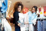 Two young girls look at clothing in store - 229413628
