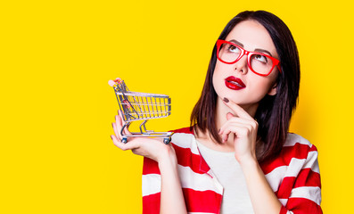 Portrait of a young woman in glasses with shopping cart on yellow background
