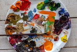 Art palette and brush with lots of colors, tempera and oil paints for painting the artist at the easel. selective Focus