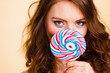 Quadro Woman holds colorful lollipop candy in hand, covering face