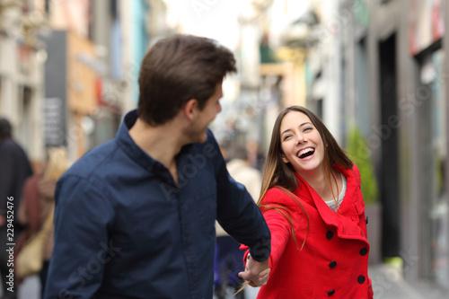 Leinwanddruck Bild Couple running together in the street