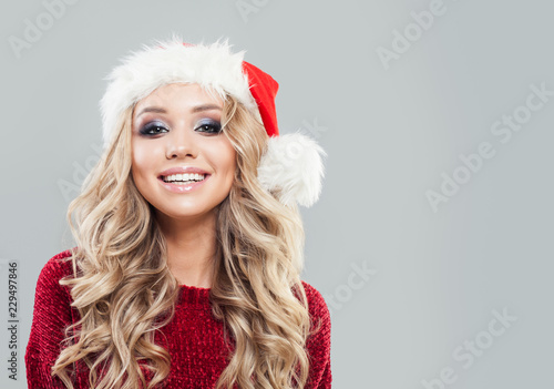 Christmas woman in santa hat having fun and smiling on background with copy space