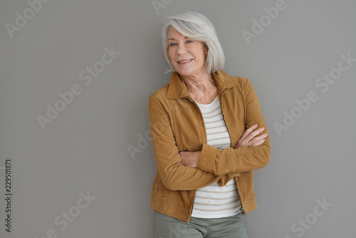 Modern senior woman smiling on isolated grey background