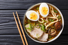 """Постер, картина, фотообои """"Asian style soup with udon noodles, pork, boiled eggs, mushrooms and green onions close-up on the table. horizontal top view"""""""