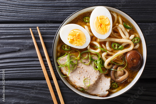 Asian style soup with udon noodles, pork, boiled eggs, mushrooms and green onions close-up on the table. horizontal top view