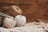 Needlework, macrame, knitting. Yarn and thread of natural colors in a wicker basket. Women's hobby. - 229512624