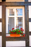 Window with pretty flowers at a frame house