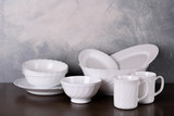 White dishware stacked on a wooden table against grey background on wooden table - 229519885