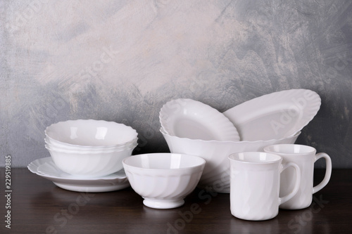 White dishware stacked on a wooden table against grey background on wooden table