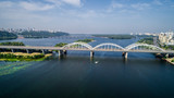 Aerial top view of automobile and railroad Darnitsky bridge across Dnieper river from above, Kiev city skyline