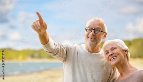 Leinwandbild Motiv old age, retirement and future concept - happy senior couple over beach background