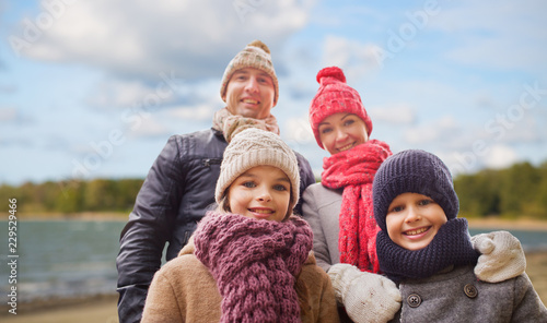 Leinwanddruck Bild family, season and people concept - happy mother, father, daughter and son over autumn beach background