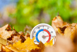 Outdoor thermometer in golden maple leaves shows warm temperature - hot indian summer concept - 229532625