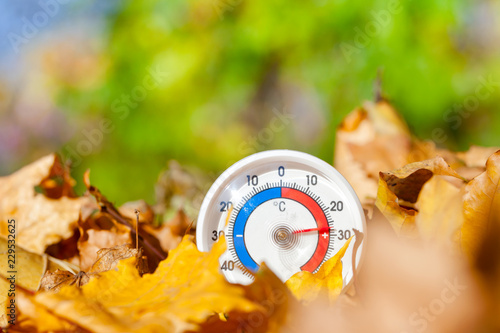 Leinwandbild Motiv Outdoor thermometer in golden maple leaves shows warm temperature - hot indian summer concept