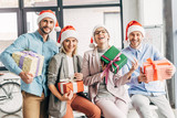 happy coworkers in santa hats holding presents and smiling at camera in office - 229544071