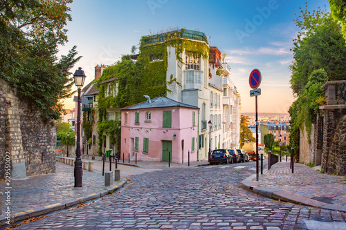 Leinwanddruck Bild Cozy old street with pink house at the sunny sunrise, quarter Montmartre in Paris, France