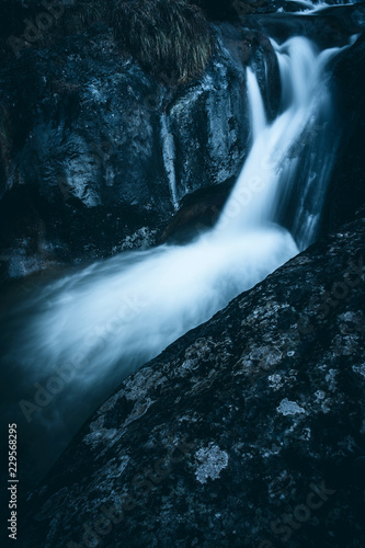 waterfall at italian alps mountains - weekend activities vacation concept - dark mood matte filter - 229568295