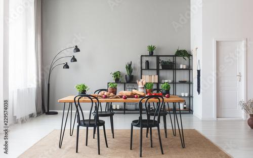 Czarni krzesła przy drewnianym stołem z jedzeniem w szarym jadalni wnętrzu z roślinami i lampą. Prawdziwe zdjęcie