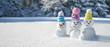Leinwandbild Motiv Winter - Schneemänner mit bunten Strickmützen