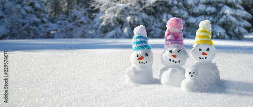 Leinwanddruck Bild Winter - Schneemänner mit bunten Strickmützen