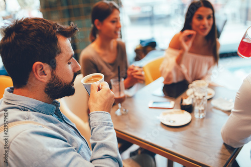 Poster Young man enjoys coffee with friends in a cafe