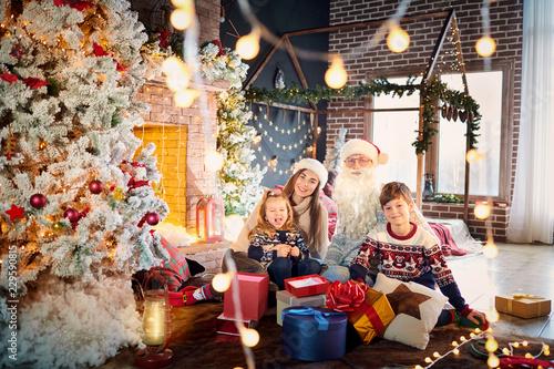 Rodzina bawić się z prezentami na podłoga indoors na dniu bożego narodzenia.