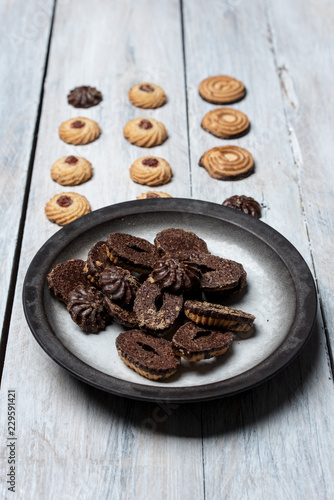shortbread butter cookies with chocolate and plum jam on a white wooden table - 229591421