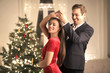 Leinwandbild Motiv Lovely couple dancing in the living room, celebrating Christmas Eve