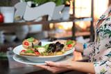 Zupa z owocami morza w dłoniach kelnerki, skorupiaki i mule. - 229605058