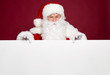 Leinwandbild Motiv Happy grandfather in Santa Clause costume holding big white blank banner on red background, Christmas and New year concept