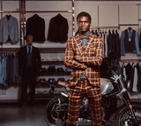 African-American man dressed in a trendy elegant suit posing with crossed arms near retro sports motorbike at the men's clothing store. - 229629413